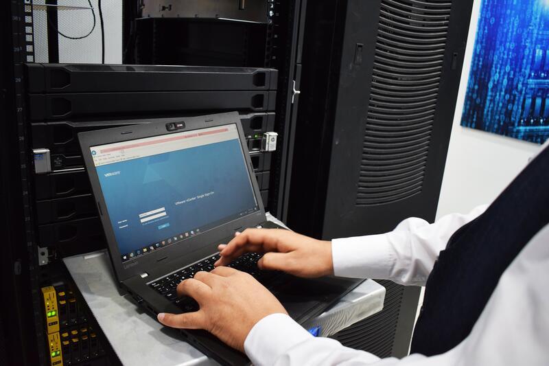 Widoczne ręcę człowieka pracującego przy laptopie obok serwerów