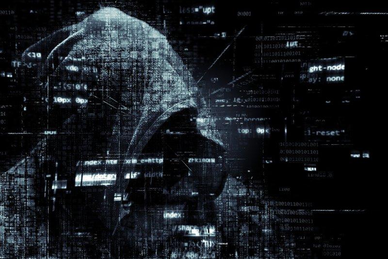Grafika ze zdjęcia osoby w kapturze oraz kodu zero jedynkowego